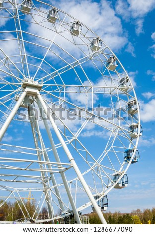 Ferris wheel an amusement-park or fairground ride consisting of a giant vertical revolving wheel with passenger cars suspended on its outer edge. #1286677090