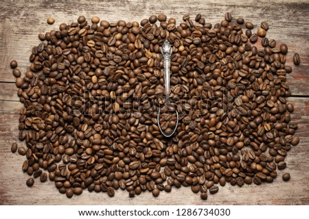 Pile of roasted coffee beans with spoon on old wooden background. Top view point. #1286734030