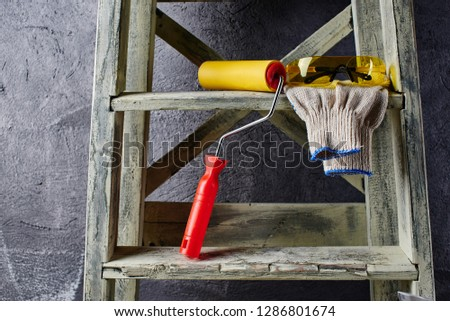 Construction tools and stepladder on a black wall background. Repairs #1286801674