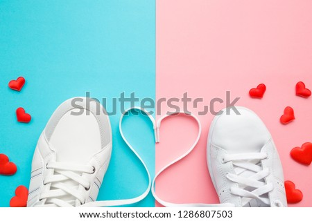 Heart created from white shoelaces between male and female sport shoes. Bright, red hearts. Love concept. Empty place for lovely, cute text, quote or sayings on pastel blue and pink paper. Closeup. #1286807503