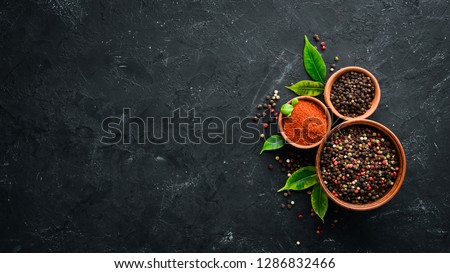 A set of peppers. Black pepper, colored pepper, ground pepper, dried chili pepper. Top view. On a black background. free space for your text. #1286832466