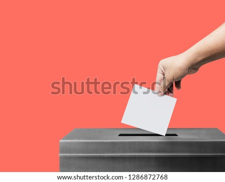 Hand holding ballot paper for election vote concept at Living Coral pantone background, clipping path Isolated. #1286872768