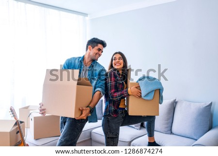 Young couple just moved into new empty apartment unpacking and cleaning - relocation. Young couple carrying big cardboard box at new home.Moving house. #1286874274