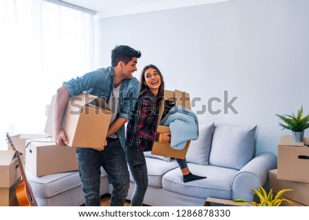 Home, people, moving and real estate concept - happy couple having fun in cardboard boxes at new home. Happy couple with cardboard boxes in new house at moving day.  #1286878330