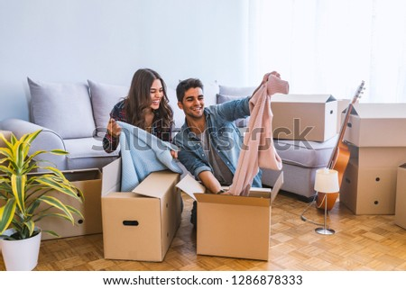 New Home. Funny young couple enjoy and celebrating moving to new home. Happy couple at empty room of new home. Happy couple is having fun with cardboard boxes in new house at moving day.  #1286878333