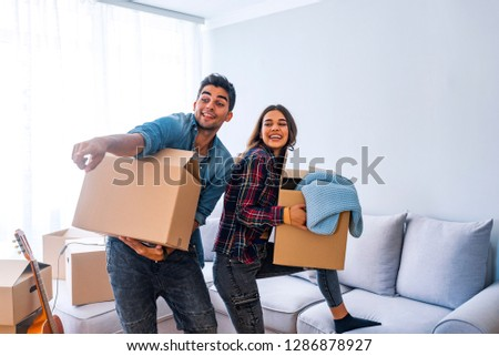 Young happy couple move to a new home. Happy young couple unpacking or packing boxes and moving into a new home. Young couple moving to a new apartment together relocation #1286878927