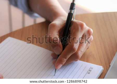 Young hands with pen writing on notebook on wood table. #1286898742