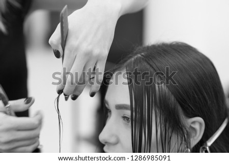 The hairdresser does a haircut of hair to a woman, a brunette in a beauty salon. #1286985091
