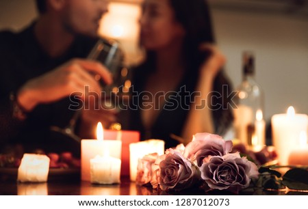Beautiful passionate couple having a romantic candlelight dinner at home, drinking wine, toasting #1287012073