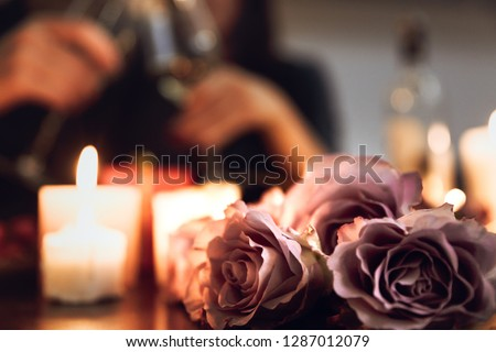 Beautiful passionate couple having a romantic candlelight dinner at home, drinking wine, toasting #1287012079