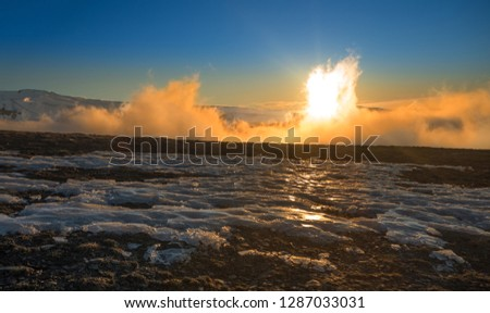 Close-up of brown land soil with snow and ice followed by a thick white mist that  traverses the orange light of the sun that is behind a snowy white mountain under the dark blue sky #1287033031