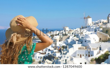 Tourist traveling in Santorini, Oia island in Greece, Europe travel summer vacation woman relaxing at view windmills. Holiday girl in hat and green flowered dress enjoying sun in Santorini. #1287049600