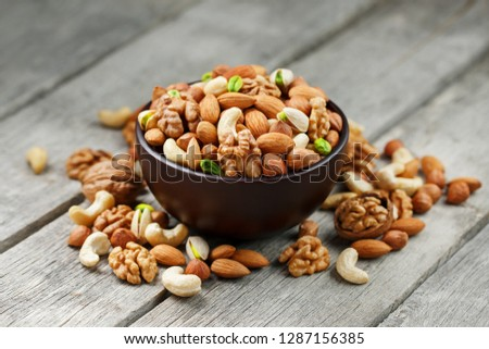 Wooden bowl with mixed nuts on a wooden gray background. Walnut, pistachios, almonds, hazelnuts and cashews, walnut. #1287156385