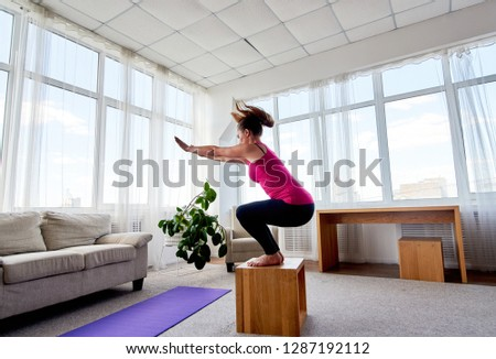 Side view of young woman doing box jump exercise in living room at home, copy space. Jumping squats. Sport, healthy lifestyle concept  #1287192112