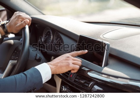 Young businessman driver sitting inside the car changing destination in navigator close-up #1287242800