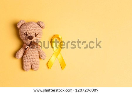 Children's toy with a Childhood Cancer Awareness Yellow Ribbon on yellow background. Childhood Cancer Day February, 15. #1287296089