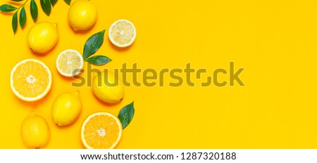 Ripe juicy lemons, orange and green leaves on bright yellow background. Lemon fruit, citrus minimal concept, vitamin C. Creative summer minimalistic background. Flat lay, top view, copy space.  #1287320188