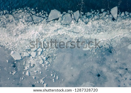 Glacier Lagoon with icebergs from above. Aerial View. Cracked Ice from drone view. Background texture concept. #1287328720