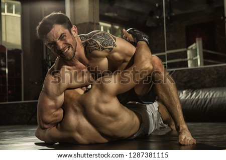 Two MMA fighters grappling on training in gym. Muscular sportsman with aggressive look looking at camera, sitting on chest of rival and choking him with hand, opponent lying in floor and resisting.  #1287381115