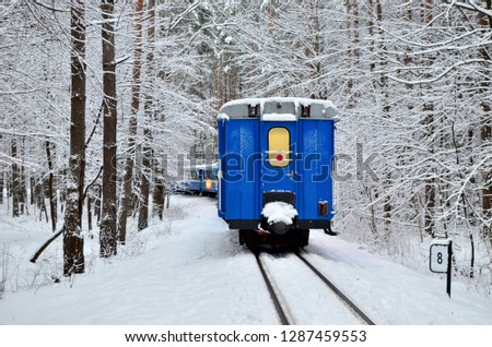 An old vintage train with beautiful blue Passenger cars rides by rail through a winter snowy forest. Fabulous winter landscape. Narrow gauge railway. Logistics railway transport