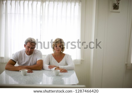 Serious mid-adult couple sitting inside at their kitchen table. #1287466420