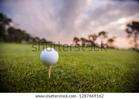 Golf ball sitting on a tee on smooth grass under a cloudy glowing sky.