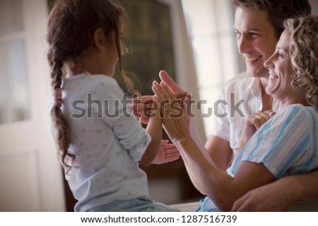 Side view of a little girl playing with her parents. #1287516739