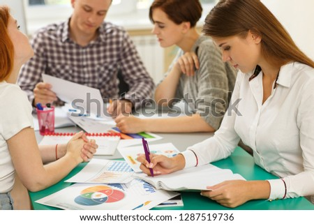 View from side of serious lady in white shirt sitting at table and writing test in notes during lesson. Young students in process of working and discussing problem in modern school. Concept of study. #1287519736