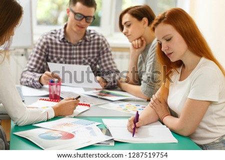 View from side of serious woman in white shirt sitting at table and doing test in modern school. Students looking at books, talking and learning new topic during interesting lesson at background. #1287519754