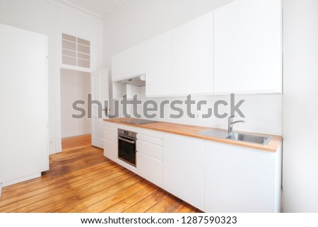 empty, new  built-in kitchen with whote furniture and wooden floor - #1287590323