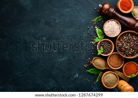 A set of peppers. Black pepper, colored pepper, ground pepper, dried chili pepper. Top view. On a black background. free space for your text. #1287674299