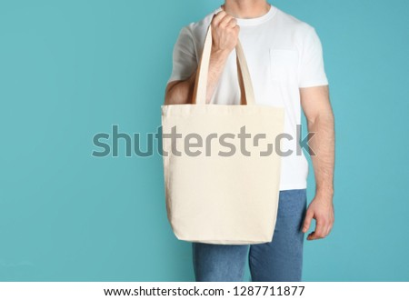 Man with cotton shopping eco bag on color background. Mockup for design #1287711877
