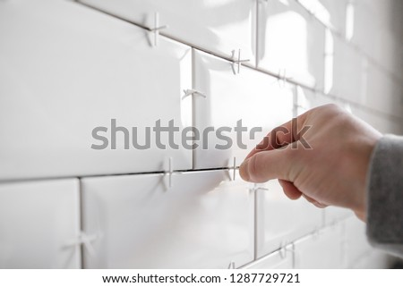Ceramic tile lying. Installing new subway or metro tile in bathroom, shower or kitchen back splash during home renovation. Placing or taking out tile spacers with hands and pliers.  #1287729721