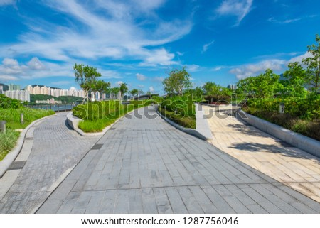 The pedestrian path in the central city park is under the blue sky and white clouds. #1287756046