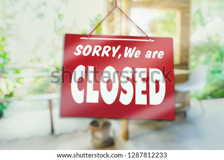 A Sign board of sorry we are closed hang on door of business shop with nature green background #1287812233