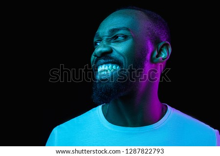 The retro wave or synth wave portrait of a young happy smiling african man at studio. High Fashion male model in colorful bright neon lights posing on black background. Art design concept #1287822793
