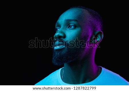 The retro wave or synth wave portrait of a young happy serious african man at studio. High Fashion male model in colorful bright neon lights posing on black background. Art design concept #1287822799