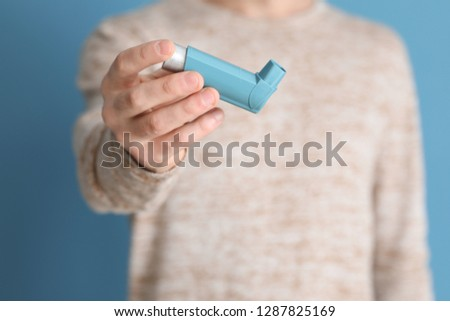 Young man with inhaler on color background, closeup #1287825169