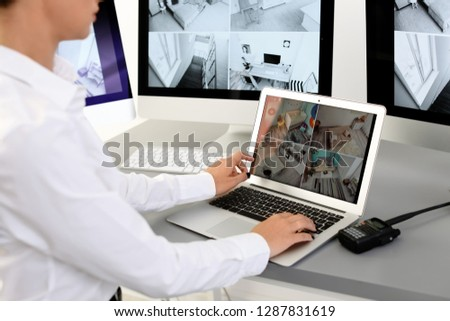 Female security guard with portable transmitter monitoring home cameras indoors, closeup #1287831619