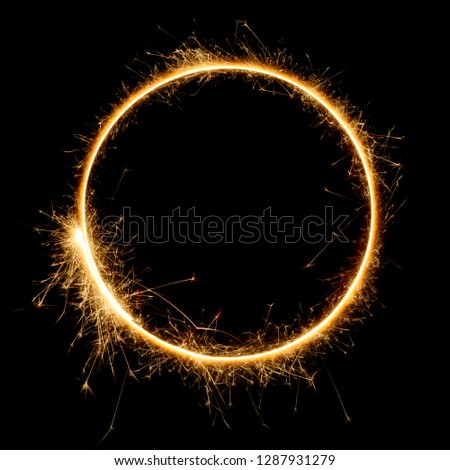 Shiny sparkler circle shape. Burning bengal fire round letter o number zero, long exposure. Burning sparklers isolated on black. #1287931279