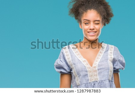 Young afro american woman over isolated background winking looking at the camera with sexy expression, cheerful and happy face. #1287987883