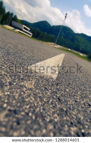 Low angle view of asphalt on proving ground with building and hills in background. Traffic, transportation and traffic safety concepts. #1288014601