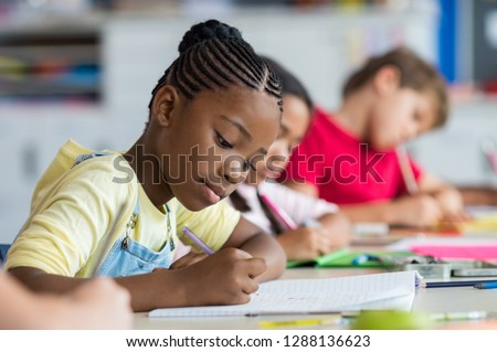 Cute pupil writing at desk in classroom at the elementary school. Student girl doing test in primary school. Children writing notes in classroom. African schoolgirl writing during the lesson. #1288136623