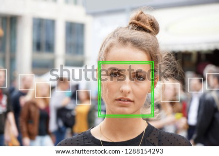 young woman picked out by face detection or facial recognition software - several other faces detected in crowd of people in background #1288154293