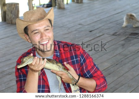 Human interacting with a baby caiman #1288166374