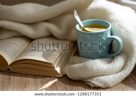 Reading a book with cup of hot tea with lemon. Still life with warm scarf, cup and old book on a wooden table. Winter, or autumn mood concept. Warm autumn or winter picture. Selective focus. At home