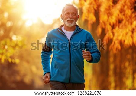 Senior runner doing stretching in autumn park. #1288221076