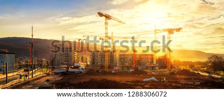 Large construction site including several cranes working on a building complex, illumined by warm gold sunlight #1288306072