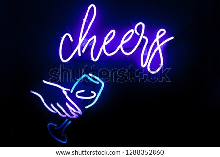 Close up neon sign design element on wall with lettering font at wine bar of blue and purple colour on dark background. Female hand holding glass of wine. cheers text on the wall. Neon tube, led wall
