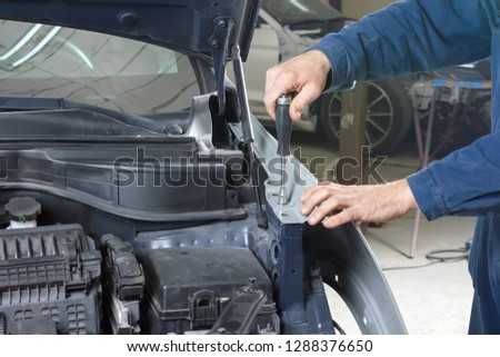 car mechanic repairs car bodywork of a vehicle after a traffic accident #1288376650